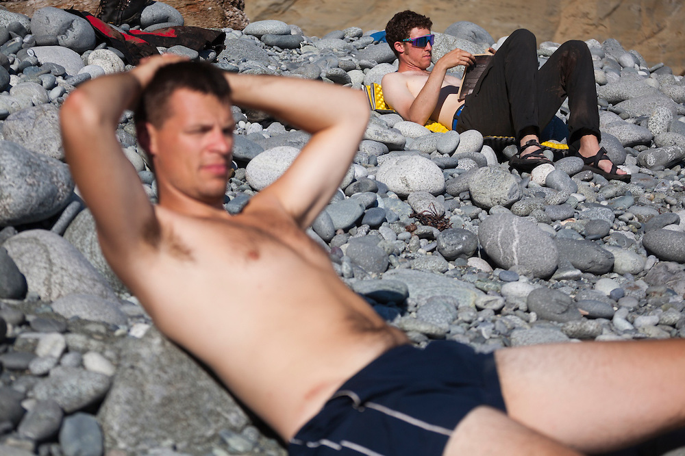 Henry (front) and Zach Podell-Eberhardt relax on the cobble beach at Cullite Cove, West Coast Trail, British Columbia, Canada.