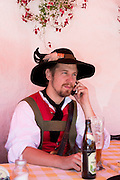 Young man using cellphone at beer festival in the village of Klais in Bavaria, Germany