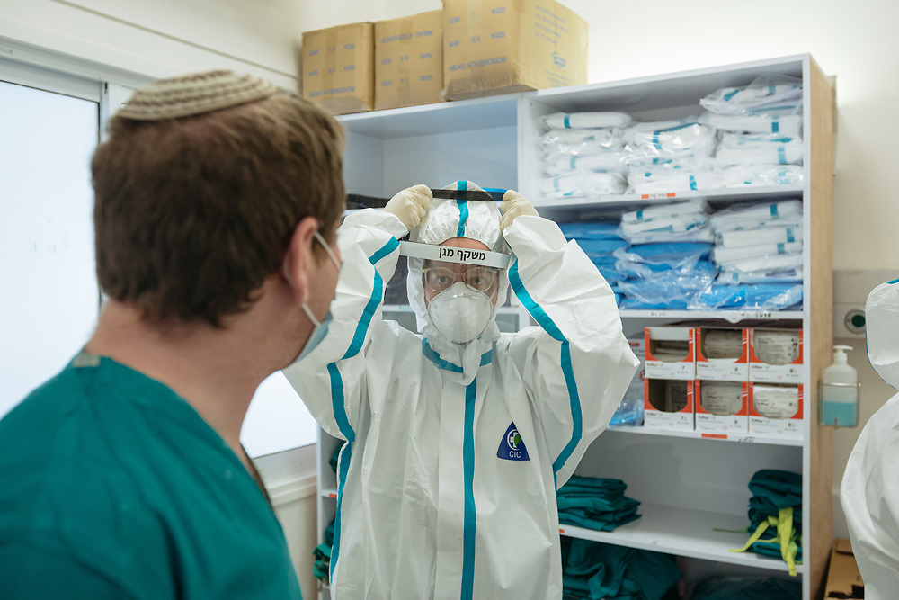 Dr. Limor Rubin puts on protective gear as she talks with Dr. Matan Fischer (seen from the back), as she prepares to enter an isolated ward to treat Covid-19 Novel Coronavirus patients, at the Hadassah Ein Kerem Hospital, in Jerusalem, Israel, on April 20, 2020.