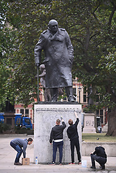 """© Licensed to London News Pictures. 08/06/2020. London, UK. A group of members of the public remove Graffiti from a statue of former British Prime Minister Winston Churchill in Parliament Square, after it was graffitied with the words """"was a racist"""" during a Black Lives Matter demonstration In central London. The death of George Floyd, who died after being restrained by a police officer In Minneapolis, Minnesota, caused widespread rioting and looting across the USA. Photo credit: Ben Cawthra/LNP"""