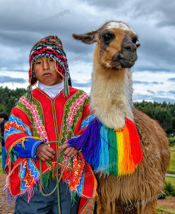 Quechua Indian Youth standing with his Llama on the heights overlooking Cusco