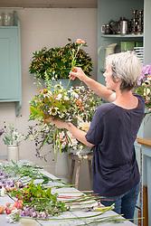 Rachel Siegfried making a hand tied  flower arrangement.