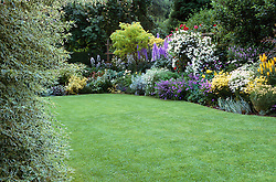 View of well kept lawn and borders at Eastgrove Cottage. Design: Carol and Malcolm Skinner