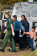 03 MARCH 2003 - PHOENIX, ARIZONA:  An Immigration and Customs Enforcement officer escorts a family of undocumented immigrants out of a drop house discovered in Phoenix, AZ. Phoenix police and fire departments responded to reports of a migrant drop house in south central Phoenix and found more than 70 undocumented immigrants in the home. The immigrants were turned over to Immigration and Customs Enforcement (ICE) for processing and eventual removal from the US.      PHOTO BY JACK KURTZ