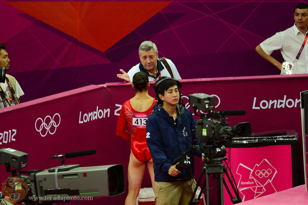 Jul 31, 2012; London, United Kingdom; USA coach Mihai Brestyan (top) instructs Alexandra Raisman (USA) after Raisman fell during a tumble while warming up in the floor exercise in the women's team gymnastics finals during the London 2012 Olympic Games at North Greenwich Arena.
