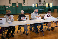Barbara Schmitz, Mary Brock, Gary Schmitz and Marylin Brown go through the ballot verification process for Ward 1 at the Laconia Community Center Thursday morning.  (Karen Bobotas Photo/for The Laconia Daily Sun)