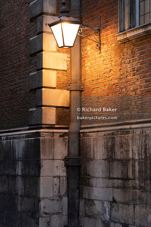 The warm glow of a street lantern illuminates a wall in Bow Churchyard, in the City of London, the capital's financial district, on 26th February 2021, in London, England.