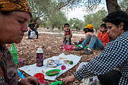 Zababdeh, West Bank, Palestine - October 23, 2010: Three generations of a Palestinian family take a break for lunch during a day harvesting olives on the outskirts of the town of Zababdeh.