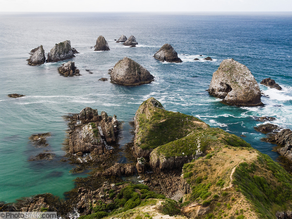 """Sea stacks and a rock arch make a pretty sight in the South Pacific Ocean at Nugget Point, the Catlins, New Zealand. Published in """"Light Travel: Photography on the Go"""" by Tom Dempsey 2009, 2010."""
