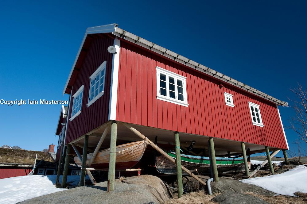 Traditional red wooden Rorbu fisherman`s hut with fishing boats stored below in village of Reine in Lofoten Islands in Norway