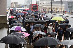 © Licensed to London News Pictures. 05/09/2016. LONDON, UK.  Commuters make their way to work across London Bridge during heavy rain showers and wet weather this morning.  Photo credit: Vickie Flores/LNP