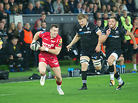 Rugby Union - 2017 / 2018 Guinness Pro14 - Ospreys vs. Scarlets<br /> <br /> Gareth Davies  of Llanelli Scarlets  attacks , chased by Rhys Webb of Ospreys at Liberty Stadium.<br /> <br /> COLORSPORT/WINSTON BYNORTH
