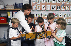 Junior school teacher with group of pupils playing recorders,