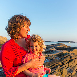 A woman and her young daughter sit on the rocks ledges on East Gosling Island in Casco Bay, Harpswell, Maine.