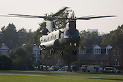 As onlookers watch, a Chinook helicopter takes-off after a brief touchdown in Ruskin Park, south London borough of Lambeth, UK.