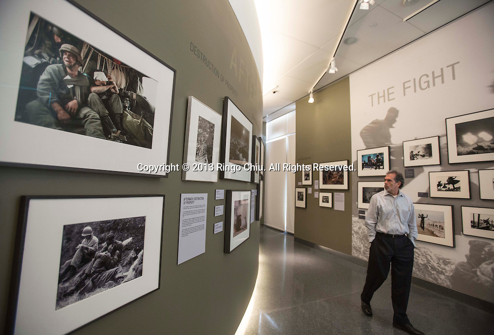 A man looks at the pictures in the Annenberg Space for Photography gallery Wednesday in Los Angeles, California. The Gallery will present the exhibit, ``War/Photography,'' featuring ``images of armed conflict and its aftermath.'' from March 23 to June 2. The exhibit includes more than 170 print images from 1887 through the present day. (Photo by Ringo Chiu/PHOTOFORMULA.com).