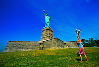 Girl doing a somersault next to the Statue of Liberty, New York harbor, New York, New York USA