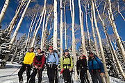 Backcountry skiers posing with aspen trees in Uncompahgre National Forest, Colorado.