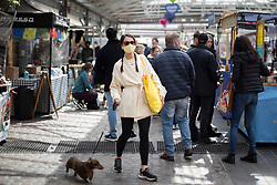 © Licensed to London News Pictures. 15/04/2021. London, UK. A woman wears a mask as she walks her dog through Greenwich Market in South East London. Earlier this week Lockdown restrictions were eased to allow non essential retail and outdoor dining to reopen. Photo credit: George Cracknell Wright/LNP