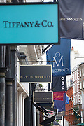 Signs for high end fashion and exclusive brands on Old Bond Street, London, UK.