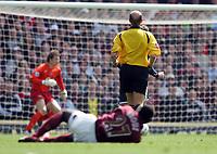 Referee Steve Bennett ignores the injured Emmanuel Eboue of Arsenal as Tottenham Hotspur score the first goal through Robbie Keane.