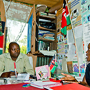 NGO worker Benedine Kipruto meets Julius Tuwei, Chief of Soba Location in Nandi County to discuss youth empowerment. Rift Valley Province, Kenya.