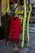 Cashmere clothing on display alongside yellow construction scaffolding sleeves in central London. Juxtaposed next to the yellow casings on the scaffolding poles, we see the incongruous nature of the shop mannequin, deserving more of a sympathetic context. Both models wear a tartan skirt or bottom which sets off nicely with the scarlet red duffel coat on the right.