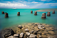 Concrete pylons of an old wharf stand sentinel in the turquoise Kalohi channel that separates the islands of Molokai and Lanai in Hawaii.
