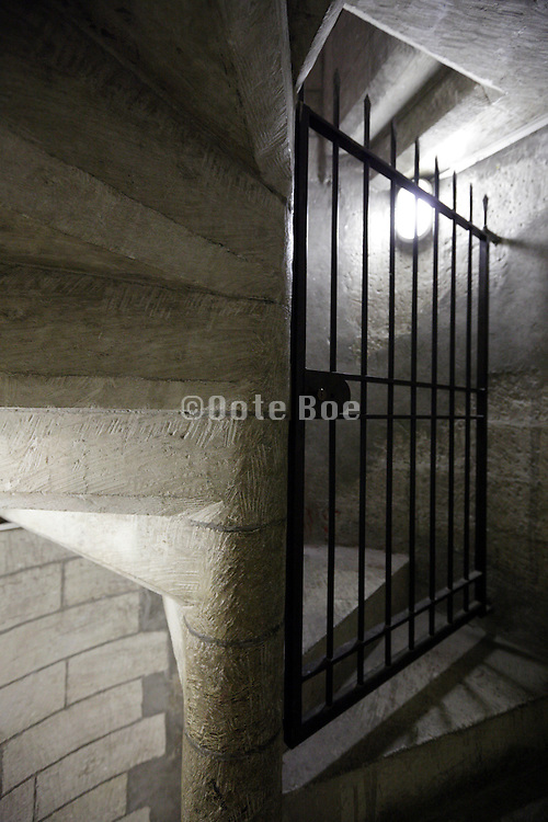old stone stairwell with closed and locked metal gate