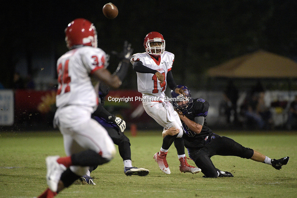 Edgewater quarterback Cortez Pembleton (14) throws to Malcolm Taylor (34) while in the grasp of Timber Creek's Ryan Hutchison (8) during the first half of a high school football game in Orlando, Fla., Friday, Oct. 10, 2014. (Photo by Phelan M. Ebenhack)