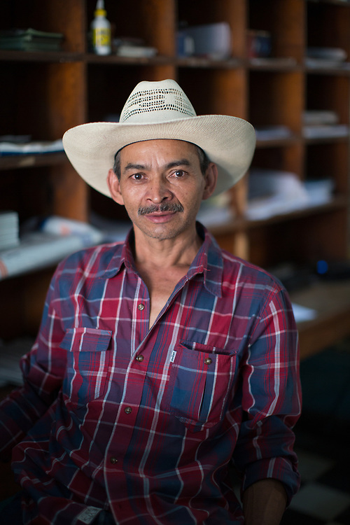 Jesús Alberto Monroy Díaz, postmaster, Copán Ruinas.<br /> <br /> I liked working from an early age. From when I was eight I worked in whatever I could. I used to pass beans to Guatemala, at midnight with a mule, and the next day I'd bring back sugar, because there was no sugar in Honduras, only in Guatemala. Now you can get everything. At that time there weren't many roads, everything had to be brought on a mule, now everything is modernised and nothing is taken on mules.<br /> <br /> Now I send packages with a barcode. They have the GPS system. The system tells you where the package is. Everything is modernised.<br /> <br /> From the age of 15 I worked cutting yucca plants, in Guatemala. We'd cut chunks of the stem and then in the factory in Guatemala City they'd put on a hormone and colour, and that made is sprout colourful flowers. They'd cover the bits of stem in cement and export them. I worked for three years in that, and then I came back here to work in the post office.<br /> <br /> I worked in Honducor (the post office), Bancrecer (a bank), in the municipality, then in the Customs office at the El Florido border post. While I was there Ricardo Maduro won the Presidency and I had to leave, and I put my papers in to work at the post office again, I've now worked here for 22 years.<br /> <br /> My life has been about work, I am happy, and yes, I feel proud.<br /> <br /> ************<br /> A mi me gustaba trabajar desde muy niño. A partir de los ocho años trabajaba en lo que pude. Pasaba frijoles para Guatemala, a medianoche en mula, y el día siguiente a traía azucar, porque no había azucar en Honduras, sólo en Guatemala. Ahora hay de todo aquí. En ese entonces no habían muchas carreterras, había que traer todo en mula, ahora esta todo modernizado y nadie va con mula. <br /> <br /> Ahora mando paquetes con código de barra. Van con un sistema de GPS. El sistema te dice por donde va. Todo esta modernizado.<br /> <br /> De los 15 años de edad me dedicaba a cortar 