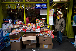 © licensed to London News Pictures. London, UK 22/01/12. A shopkeeper waits for customers as people fill Chinatown in London for shopping and sharing the excitement of Chinese New Year on the day before Chinese New Year's Eve.. Photo credit: Tolga Akmen/LNP