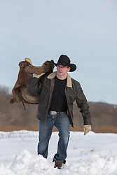 cowboy with a saddle walking through the snow