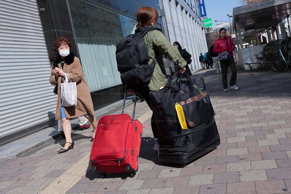 People carry bags and cases and head towards the train station and airports in Shinjuku to escape the effects of the nuclear reactor disaster in Fukushima after a magnitude 9 earthquake and large tsunami hit the Tohoku region of north east Japan  on March 11th killing nearly 20,000 people and causing massive destruction along the whole coast, and a melt-down at the Fukushima Daichi nuclear power station  Shinjuku, Tokyo, Japan March 16th 2011