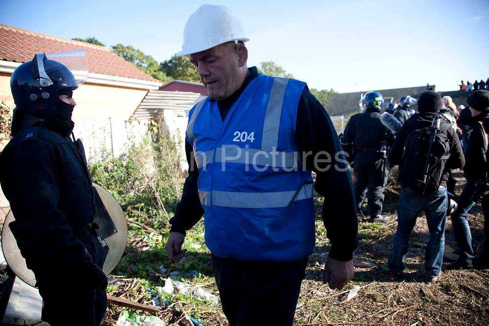 Bailiff passes police lines. Travellers at Dale Farm site prior to eviction. Riot police and bailiffs were present on 20th October 2011, as the site was cleared of the last protesters chained to barricades. Dale Farm is part of a Romany Gypsy and Irish Traveller site in Crays Hill, Essex, UK<br /> <br /> Dale Farm housed over 1,000 people, the largest Traveller concentration in the UK. The whole of the site is owned by residents and is located within the Green Belt. It is in two parts: in one, residents constructed buildings with planning permission to do so; in the other, residents were refused planning permission due to the green belt policy, and built on the site anyway.