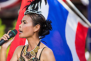 "24 JULY 2014 - BANGKOK, THAILAND:  A Thai pop singer performs patriotic songs during the happiness party in Bangkok. The Thai Junta is organizing a series of public events throughout Thailand meant to bolster public opinion. The events are called ""restoring happiness to the people"" parties. They feature historic pageants, music, food, health checks and free haircuts. The party in Bangkok is on Sanam Luang, the Royal Parade Ground, which is near the Grand Palace and the Ministry of Defense.   PHOTO BY JACK KURTZ"