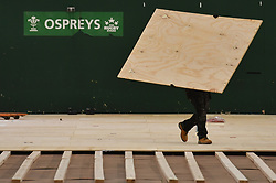 Workers lay flooring during the construction of a field hospital, which will hold up to 340 beds for coronavirus patients, at Llandarcy Academy of Sport, Neath, as the health services in the Swansea Bay area prepare their response to the coronavirus outbreak.