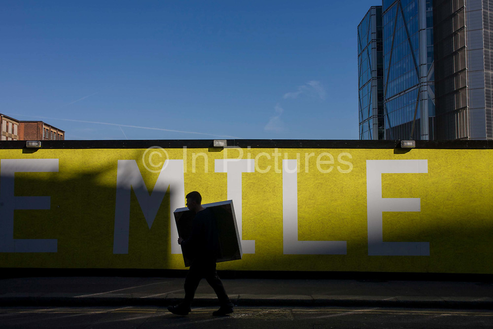 A man carries an awkward square box past a large yellow sign with spelling the word Mile. Confusingly, it appears that the person's body is in fact inside the box. Blue sky forms one half of the picture with a background also of a large office block development. It is late afternoon and pockets of spring sunshine are shining on this street in the capital's financial heart - the City of London, known as the Square Mile, founded by the Romans in AD43.