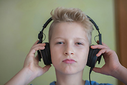 Portrait of a boy listening to music with headphones, Freiburg im Breisgau, Baden-Württemberg, Germany
