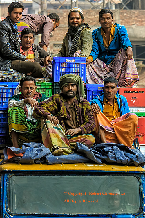 Third Class: Men stake out their spots for the long trip atop a fully loaded lorry, Dhaka Bangladesh.