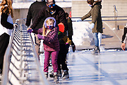 03 JANUARY 2021 - DES MOINES, IOWA: A child holds onto the railing while skating at Brenton Skating Plaza in downtown Des Moines. The ice skating rink usually opens in late November and stays open through late February or March, depending on weather. Covid restrictions limited capacity to less than half, skaters were encouraged to social distance, and skaters were required to wear proper face masks. This year the rink was forced to close January 3, after only six weeks, because it wasn't possible to comply with COVID-19 restrictions and still be profitable. Restrictions caused by the Coronavirus pandemic have limited many public events this winter in Iowa.     PHOTO BY JACK KURTZ