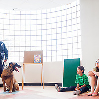 062913       Cable Hoover<br /> <br /> Gallup Police K-9 officer Terrance Peyketewa laughs while describing his dog Mac to a crowd at the Octavia Fellin Public Children's Library in Gallup Saturday. The presentation was part of the ongoing Summer Reading Program at the library.