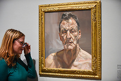 """© Licensed to London News Pictures. 23/10/2019. LONDON, UK. A staff member views """"Reflection (Self-Portrait)"""", 1985, by Lucien Freud. Preview of """"Lucian Freud: The Self-portraits"""" at the Royal Academy of Arts in Piccadilly.  56 works on display chart Freud's artistic development over almost seven decades on canvas and paper in a show which runs 27 October to 26 January 2020.  Photo credit: Stephen Chung/LNP"""