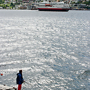 Three weeks aboard the Kong Harald. Hurtigruten, the Coastal Express. Bergen. Fisherman along the shore of Bergen.
