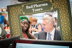"""24 July 2018, Amsterdam, the Netherlands: """"Are you swallowing pharma's lies?"""" ask protestors in the Exhibition area of the International AIDS Conference 2018, AIDS 2018, as they visit the Abbott company's exhibition area. The group carry out a """"Bad Pharma Tour"""", showcasing pharmaceutical companies' whose humble slogans about good life prospects, say the protestors, do not match up with the way the companies maintain high prices and questionable ethics in order to produce revenue and offer high wages for CEOs and other company representatives."""