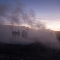 Bolivia, Salar de Uyuni - Tourists mingle in the geysers near the Salar de Uyuni at daybreak. Photo by Susana Raab