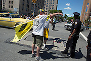 A man with an Occupy Wall Street sign argues with police, who asked him to join the Occupy Wall Street contingent in the parade.