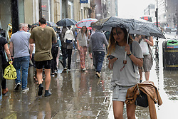© Licensed to London News Pictures. 02/06/2017. London UK. Commuters, shoppers and tourists react to a sudden thunderstorm which brings a heavy downpour to Oxford Street.   Photo credit : Stephen Chung/LNP