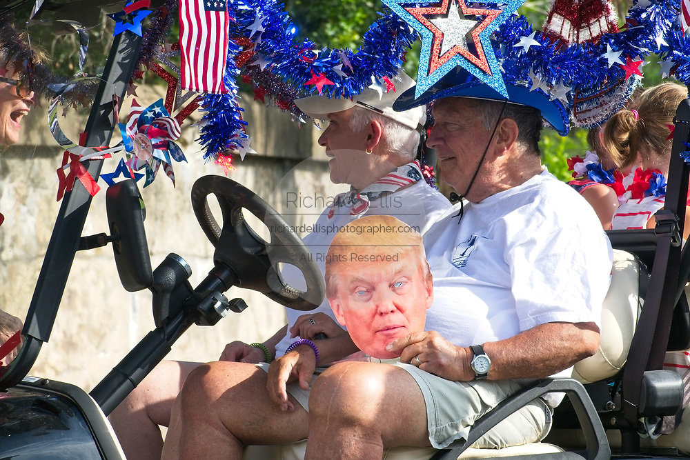 An elderly man rides along with a Donald Trump mask during the annual Sullivan's Island Independence Day parade July 4, 2017 in Sullivan's Island, South Carolina. The tiny affluent sea island hosts a bicycle and golf cart parade through the historic village.