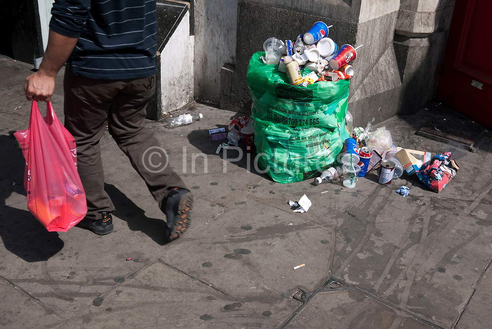 Litter gathers on and around a refuse bag on a London street. Trash is a real problem in some areas with so many people generating rubbish.